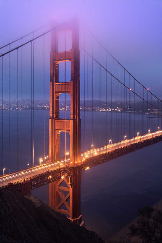 This photo is a long exposure of the Golden Gate Bridge, San Francisco Bay, California.  Lights from the cars trace light trails along the deck of the bridge.  Lights on top of the bridge's towers light up mist above the bridge creating a soft glow in the sky above.