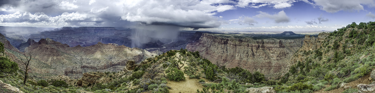 A panorama of the Grand Canyon.  A rain cloud above the Colorado River pours down rain into the canyon.