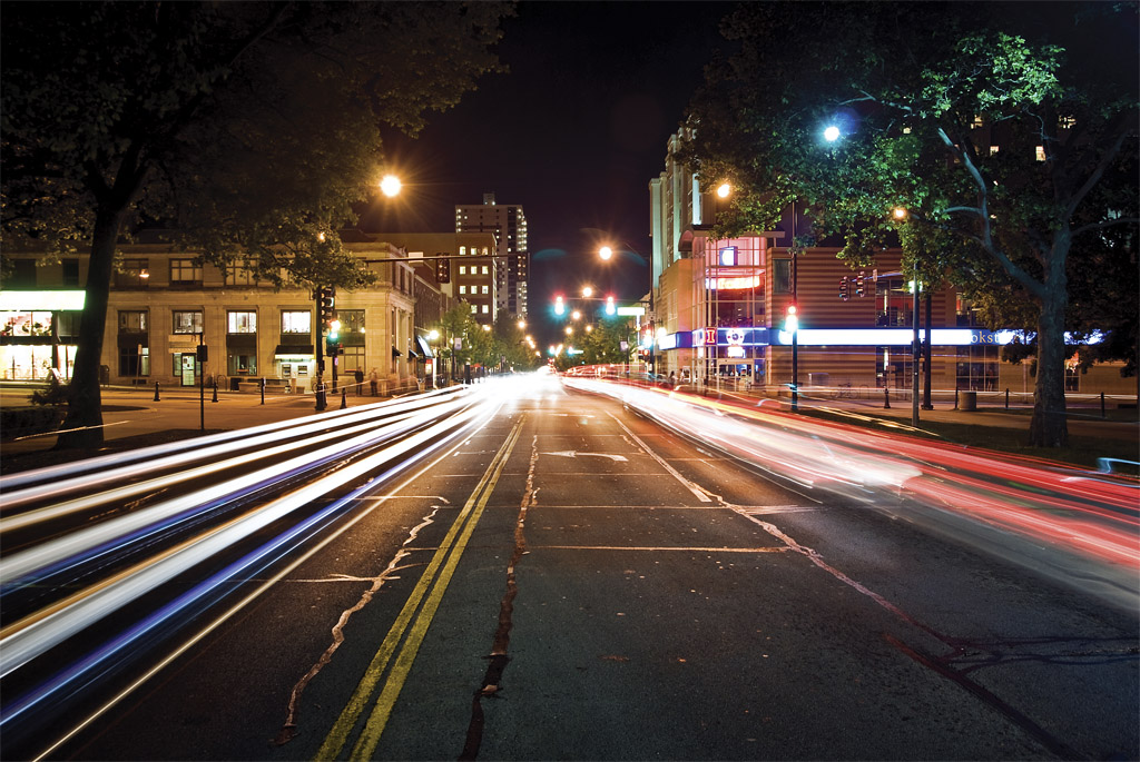 A photograph looking down Green Steet towards Campus Town near the University of Illinois at Urbana-Champaign (UIUC).  Light trails created by the lights of cars passing hover just above the road's surface.  Those light trails, street lights, traffic lights, and various buildings light up the scene.