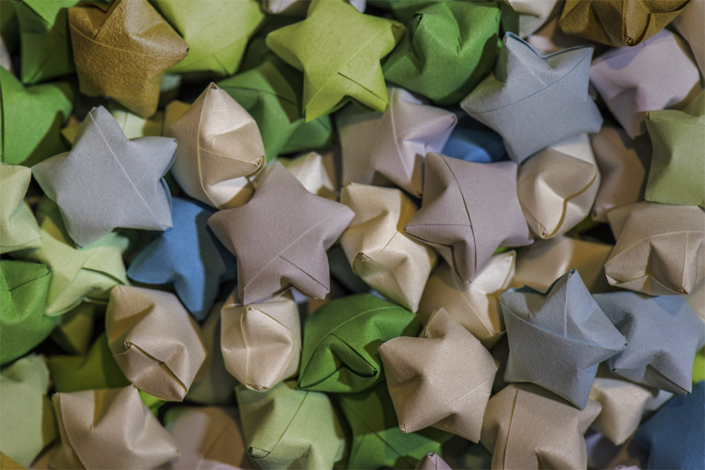 A closeup photograph of many colorful, paper stars sitting in a pile.