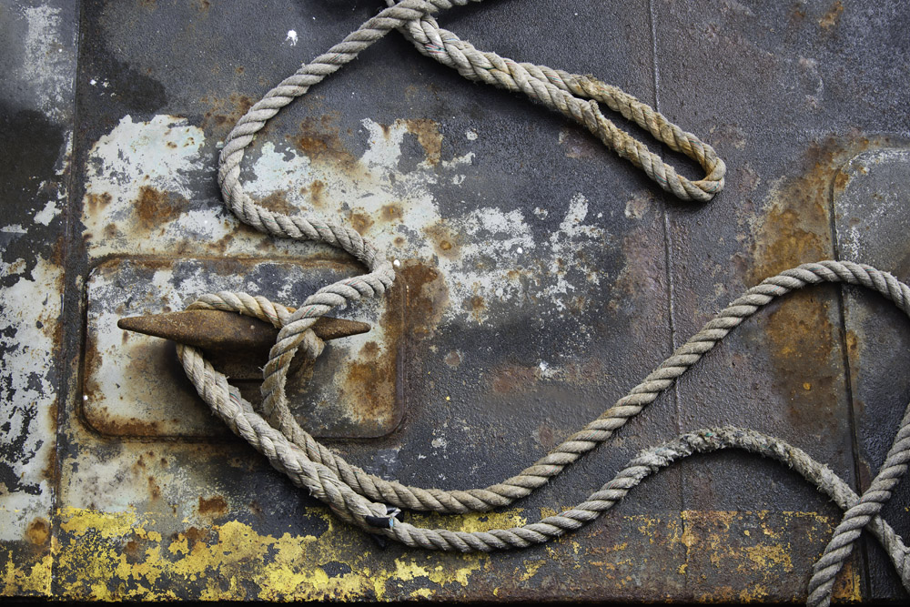 A heavy rope is strewn and snaking over the surface of a dock.  Paint peeling and other signs of wear and tear are evident on the deck.