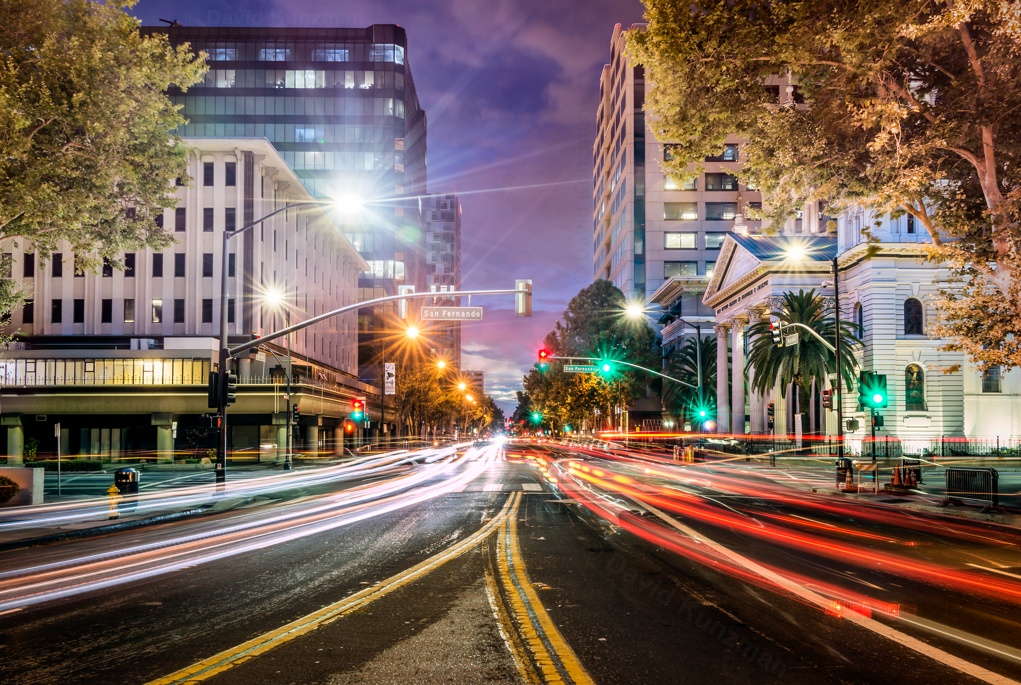 A long exposure photograph looking down Market Street in downtown San Jose, California.  The lights from passing cars create light trails floating just above the street.