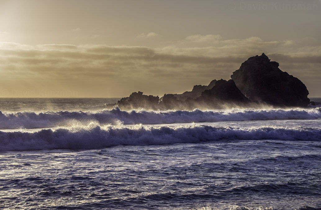 Waves in the Pacific Ocean crashing along the shore at Pfeiffer Beach, California shortly before sunset.