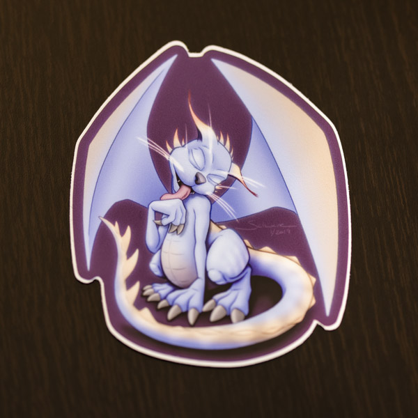 Photograph of the cat dragon sticker available in the Copious Ink Etsy store.