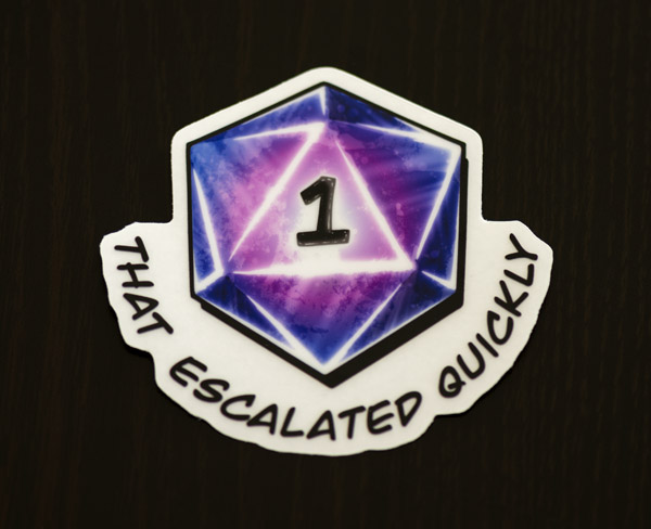 Photo of the D20 that escalated quickly sticker available in the Copious Ink Etsy store.