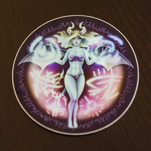 Photograph of the succubus sticker (holographic) available in the Copious Ink Etsy store.